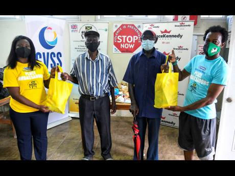 Jonelle Llewellyn (left), research associate at the Violence Prevention Alliance, presents care packages to Julius Roye (second left), Leroy Thompson (second right) and O'Neal Beaver, residents of Cassava Piece. The donation of the care packages was one