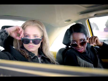 Kristen Bell (left) and Kirby Howell-Baptiste in a scene from 'Queenpins'.