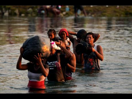 Migrants, many from Haiti, wade across the Rio Grande from Del Rio, Texas, to return to Ciudad Acuna, Mexico, on Tuesday to avoid deportation from the US.