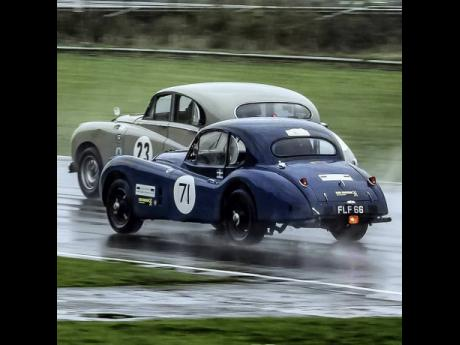 The restored 1955 Jaguar XK 140 (in forefront) battling with a Jaguar MK7 in very wet conditions at Castle Combe in 2018.