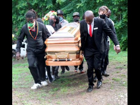 Pall-bearers carry the coffin of reggae legend Rainford Hugh 'Lee Scratch' Perry towards the grave for interment in a family plot in Cauldwell, Hanover, yesterday.