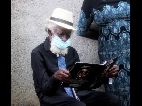 Lesbert Perry peruses his younger brother's funeral programme during the thanksgiving service for Rainford Hugh 'Lee Scratch' Perry in Hanover yesterday.