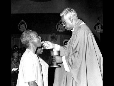 President Julius K. Nyerere of the United Republic of Tanzania (left) taking a holy Communion from the Roman Catholic Archbishop of Kingston, the Most Rev Samuel Carter, at the Holy Trinity Cathedral. Madame Nyerere, kneeling beside her husband, also took