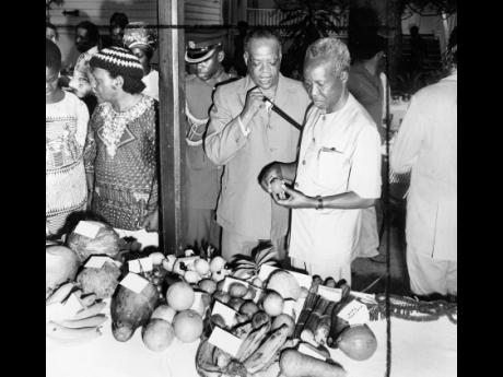Jamaican fruits are examined by the Tanzanian President Julius K. Nyerere at Devon House when he attended a luncheon of Jamaican dishes. Telling him about the naseberry and other fruits is the Minister of Education Howard Cooke.
