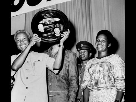 Smiles of appreciation light up the faces of President Nyerere and Madame Nyerere as he holds aloft the Jamaica-Tanzania plaque presented to him by Prime Minister Michael Manley at the National Arena.