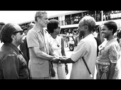 A firm and warm handshake between Prime Minister Michael Manley and Tanzanian President Julius K. Nyerere as final farewells are made at Sangster International Airport in Montego Bay on September 18, 1974. At left is Senator Dudley Thompson and at right M