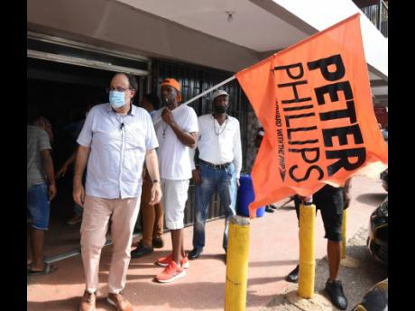 A Peter Phillips loyalist waves a flag honouring the former party leader as PNP President Mark Golding meets and greets supporters in Royal Flat, Manchester, during a tour.