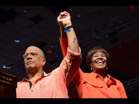 Dr Peter Phillips the new President of the PNP holding the hands of the outgoing president Portia Simpson Miller at the People National Party special delegates conference at the National Arena on Sunday, March 26, 2017