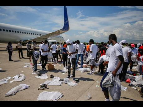 Haitians deported from the United States recover their belongings scattered on the tarmac of the Toussaint Louverture airport in Port-au-Prince, Haiti, Tuesday, September 21.