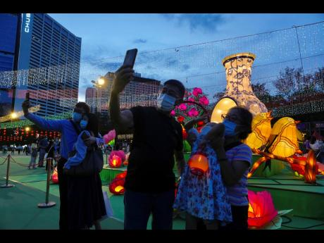 People take selfies in front of glowing lanterns during the Mid-Autumn Festival at Victoria Park in Hong Kong.