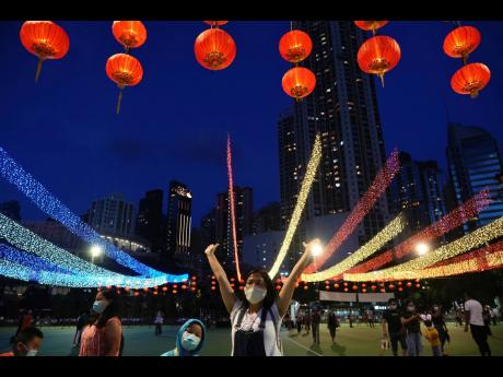 People take photos with decorations during the Mid-Autumn Festival at Victoria Park in Hong Kong