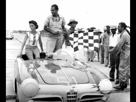 In this Gleaner photograph, Richard Sirgany, with the chequered winner's flag, stands beside his wife Yvonne in the Alfa Romeo he drove to victory in the 55-mile Jamaica Grand Prix at Vernam Field on September 24, 1961.