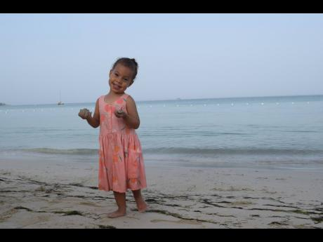 Little Morgana Melvin enjoys an early morning playing on the white sand beach of the Charela Inn.