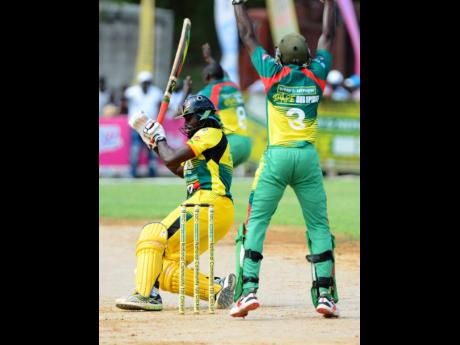 Myron Wilson (left) from Orange Hill, falls to the ground as he was trapped LBW in the SDC Community T20 cricket final against Gayle. The final was played at the Naranda Sports Complex in Discovery Bay, St Ann, on Sunday, August 25, 2019.
