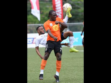 Jamar Purchell (left) from Cavalier, tries a bicycle kick as Kemar Flemmings from Tivoli Gardens challenges for the ball during their Jamaica Premier League semi-finals first leg match at the UWI-JFF-Captain Horace Burrell Centre of Excellence on yesterda
