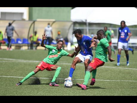 Mount Pleasant's Alwayne Harvey (centre) is strongly tackled by Shamari Dallas (left) and Lorenzo Lewin of Humble Lion during a Jamaica Premier League match held at the UWI-JFF-Captain Horace Burrell Centre of Excellence recently.