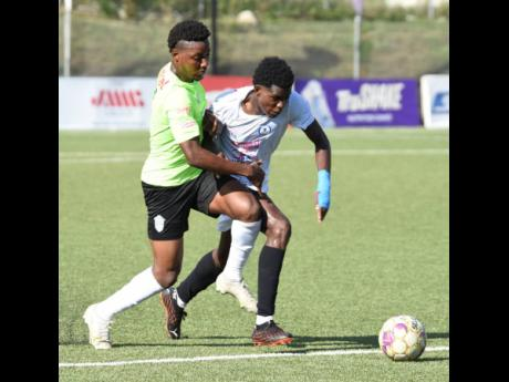 Ian Allen/PHOTOGRAPHER Shaqueil Bradford (left) from Waterhouse and Ladale Ritchie from Mount Pleasant in a keen tussle for the ball during their first leg semi-final match in the Jamaica Premier League yesterday at the UWI-JFF-Captain Horace Burrell Centr