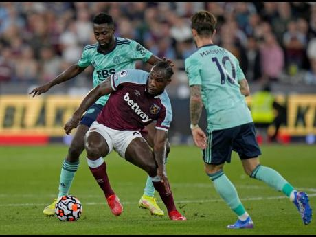West Ham's Michail Antonio (centre) holds off Leicester's Wilfred Ndidi during the English Premier League match between West Ham United and Leicester City and at the London Stadium in London, Monday, August 23, 2021.