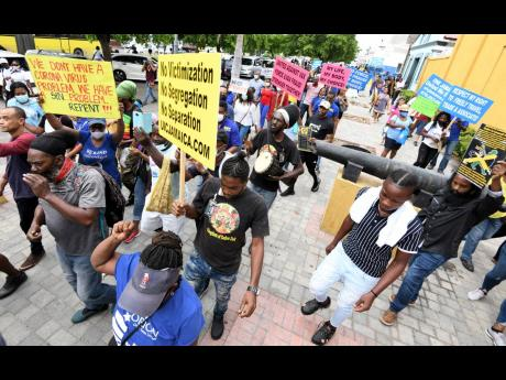 A group of antivaxxers protest at St William Grant Park in downtown Kingston.