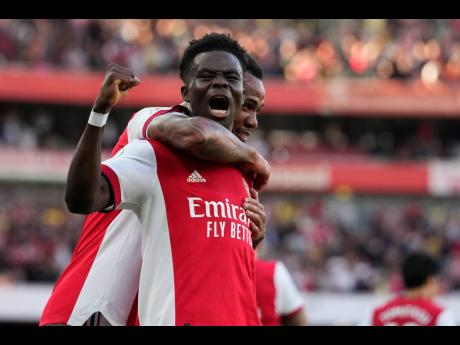 Arsenal's Bukayo Saka (front) celebrates after scoring his side's third goal during their English Premier League match against north London rivals Tottenham Hotspur at the Emirates Stadium in London, England, yesterday.