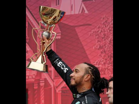 Mercedes driver Lewis Hamilton of Britain celebrates with the trophy after winning the Russian Formula One Grand Prix at the Sochi Autodrom Circuit in Russia yesterday.