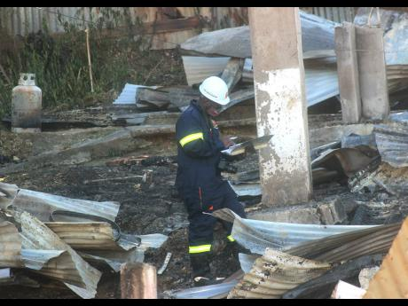 A firefighter makes recordings in a logbook at an arson scene in Granville, St James, on Sunday.