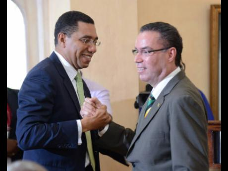 Prime Minister Andrew Holness (left) congratulates Daryl Vaz at a swearing-in ceremony of Cabinet ministers and ministers of state at King's House on Monday, March 7, 2016. Holness is under pressure to address the latest twist in the Daryl Vaz visa saga.