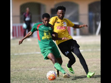 In this file photo from June 2018, Wadadah defender Tyshan Hill (left) shields the ball from Barbican FC's Cornelius Simms during a Magnum/Charley's JB Rum/Jamaica Football Federation Premier League playoff game at the Barbican Sports Complex in St And