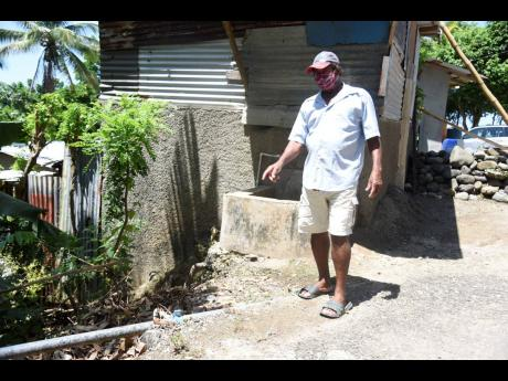 Charles Norris shows the pipeline that runs into Coopers Hill, Portland, that has been dry for over a year.