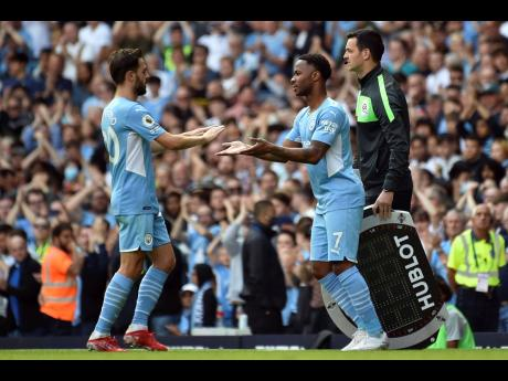 Manchester City's Raheem Sterling (right) comes on, replacing Bernardo Silva. during the English Premier League match against Arsenal at Etihad stadium in Manchester, England, on Saturday, August 28.