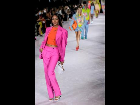 Jamaica-blooded supermodel Naomi Campbell wears a hot-pink suit and orange shirt for the Versace Spring/Summer 2022 collection during Milan Fashion Week, in Italy, on Friday.