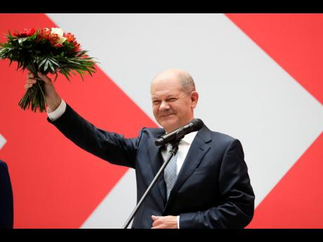 Olaf Scholz of the Social Democratic Party, top candidate for chancellor, holds a bunch of flowers after a press statement at the party's headquarter in Berlin, Germany, yesterday.