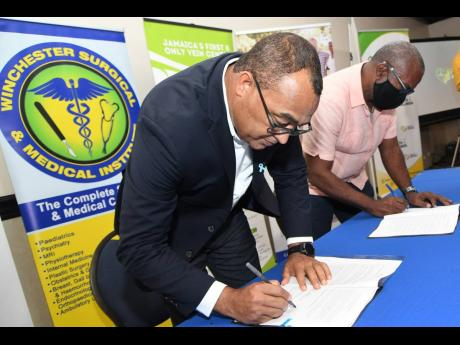 Dr Christopher Tufton, minister of health and wellness, inks an agreement with Dr Orville Nembhard, director of Health Plus Associates, during a ceremony involving 11 private-sector partners who the ministry will engage to administer COVID-19 vaccines. The