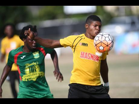 Wadadah defender Jamar Johnson (left) stays close to Barbican FC player Shaquille Lewis, trying to take the ball off him, during their Magnum/Charley's JB Rum/Jamaica Football Federation Premier League playoff at the Barbican Sports Complex on Sunday, Ju