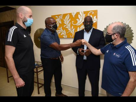 Jamaica Football Federation Vice President Raymond Anderson (second left) greets UEFA Assist official Pedro Correia (right) as Concacaf official Howard McIntosh (second right) and UEFA Assist official Kenny MacLeod look on during a training seminar for Jam
