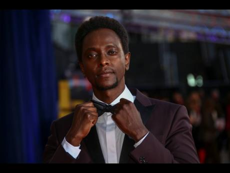 Edi Gathegi adjust his bow tie upon arriving at the opening of the London Film Festival and the world première of the film 'The Harder They Fall' in London on Wednesday.