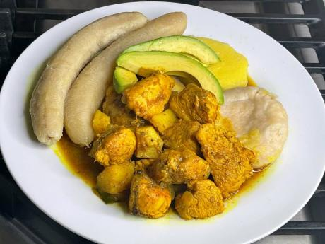 Curried chicken, paired with boiled green bananas and a dumpling, served with slices of avocado.