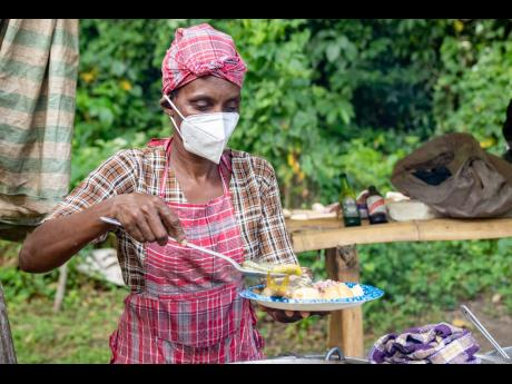 The well-known Miss Belinda shares a plate of tasty authentic Jamaican food by the riverside.