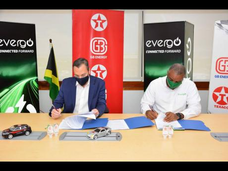 CEO of GB Energy Texaco Jamaica, Bela Szabo (left) and Director, Strategic Planning, Facilities and IT at Jamaica Energy Partners, Kevin Francis, officially sign an agreement between both companies for the installation of electric vehicle chargers at a nu