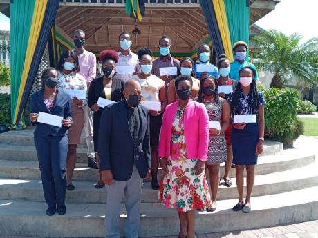 Father Hollis Lynch (front row), a founding member of the Joe and Angella Whitter Foundation, and Angella Whitter, chairman of the foundation, along with some of the 26 scholarship recipients.