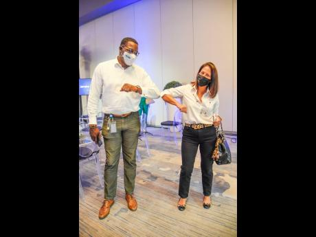 Stephen Price, CEO of FLOW, bumps elbows with Tina Myers Matalon, marketing director of Restaurants of Jamaica.