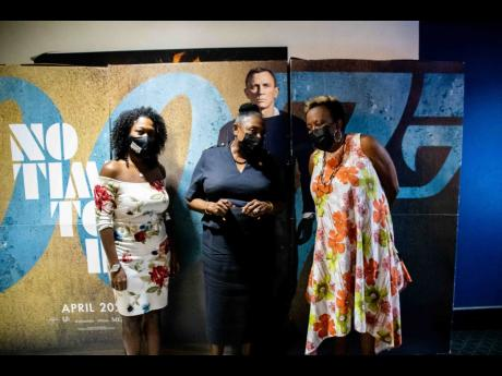 Minister Grange (centre) in discussion with the Managing Director of Cinecom Productions, Natalie Thompson, line producer in Jamaica of 'No Time To Die', last Thursday at Carib 5 cinema. At left is Film Commissioner Renee Robinson. Parts of the film we