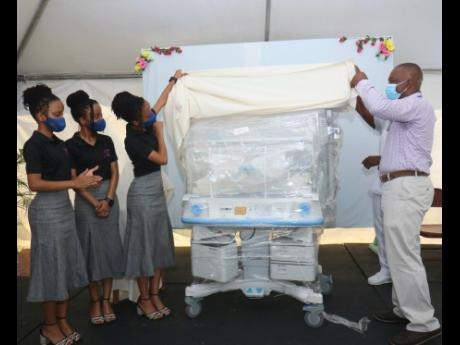 Mikaili, Malaika and Mahari Foster and Dr Ludrick Morris, paediatric consultant, unveils the infant incubator at the handover ceremony at the Savanna-la-Mar Public General Hospital on Friday.