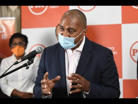 Julian Robinson, opposition spokesman on finance, addresses a press conference at the Office of the Leader of the Opposition on Monday.