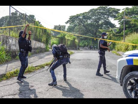 Policemen enter the cordoned area where Christopher 'Dog Paw' Linton was killed on Monday.