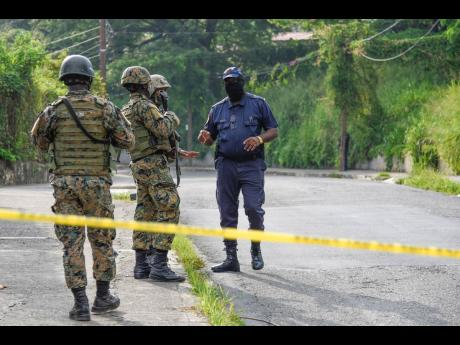 A cop engages in dialogue with soldiers at the scene where reputed gang leader Christopher Linton, more popularly known as 'Dog Paw', was shot and killed in an alleged confrontation with the police in Elletson Flats, eastern St Andrew, on Monday.