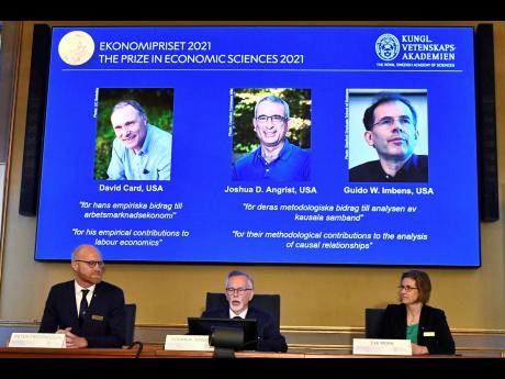 Permanent Secretary of the Royal Swedish Academy of Sciences, Goran K Hansson, centre, announces the 2021 Nobel Prize for economics, flanked by members of the Royal Swedish Academy of Sciences, Peter Fredriksson, left, and Eva Mork, during a press conferen