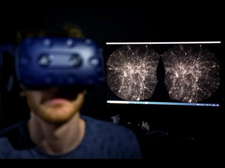 Hadrien Gurnel, software engineer at EPFL's Laboratory for Experimental Museology (eM+), explores with a virtual reality helmet the most detailed 3D map of the universe with the virtual reality software VIRUP, or Virtual Reality Universe Project.