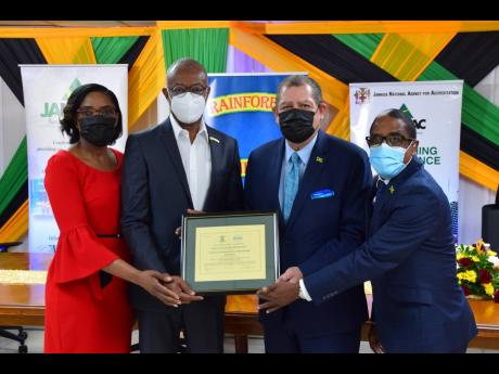 From left: Sharomae Shirley, chief executive officer, Jamaica National Agency for Accreditation, presents the certification to Rainforest Seafoods General Manager Jerome Miles. Sharing in the occasion is Minister of Industry, Investment and Commerce Audley