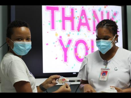 Angella Byfield (left), a member of the Preemie Foundation of Jamaica, gives an ID pin to Nurse Shelly Latchman as she collects her lunch during the treat.